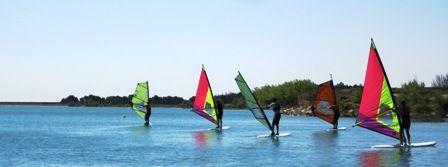 Cursos de windsurf y vela ligera en La Sotonera y campamento de inglés en Biscarrués con actividades deportivas.